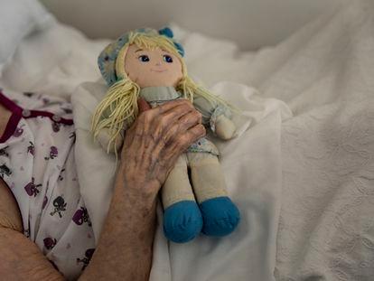 Una anciana sostiene una muñeca en la habitación de la residencia en la que permanece confinada a causa de la pandemia, en Badalona, España, el 26 de marzo de 2020, una de las imágenes de Santi Palacios, ganador de la XXIV edición de los Premios Luis Valtueña de Fotografía Humanitaria.