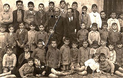 Severiano Núñez, con gafas, el maestro fusilado en Plasencia, junto a su colega y los niños de la escuela.