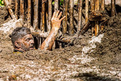 Un concursante intenta salir de una jaula de madera en un auténtico barrizal para superar una prueba de equipo.