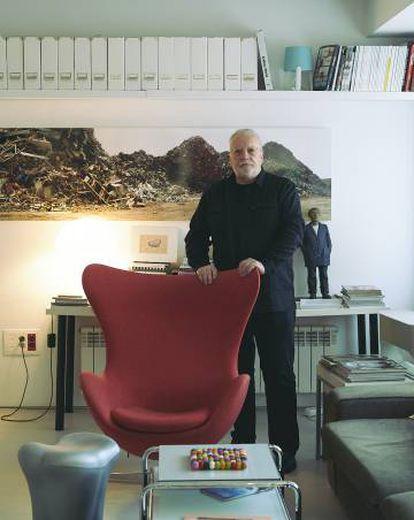 Pérez de Albéniz se apoya sobre la Egg Chair de Fritz Hansen. En primer plano, salvamanteles de la tienda del MoMA. En la pared, obra de Basurama.