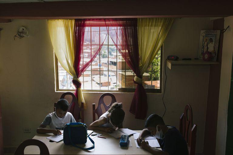 Niños practican fracciones en la escuela improvisada por Iris Pellicer en el barrio José Félix Ribas de Petare, Caracas.