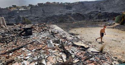 Un hombre, en la parcela que ocupaba la casa de su vecino, de la que solo han quedado las tejas y una estufa, ayer, en la urbanización Altury de Turís.