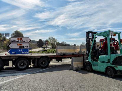Un operario retira los bloques de hormigón que impedían el tráfico hacia Igualada (Barcelona).