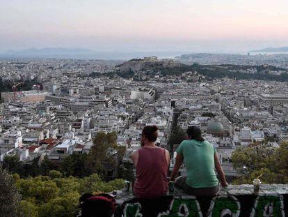 Dos jóvenes observan Atenas desde una colina, a comienzos de este mes. En vídeo, declaraciones del comisario europeo de Asuntos Económicos, Pierre Moscovici.