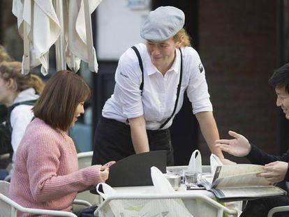 Una camarera toma nota a un par de turistas en Sevilla.