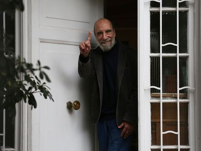 El poeta chileno Raúl Zurita saluda desde la puerta de su casa, este martes.