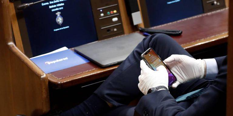 Un diputado consulta su móvil con unos guantes durante el pleno extraordinario para explicar la declaración del estado de alarma.