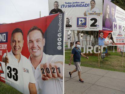 Un hombre camina frente a varios carteles electorales el pasado 15 de marzo en Lima (Perú).