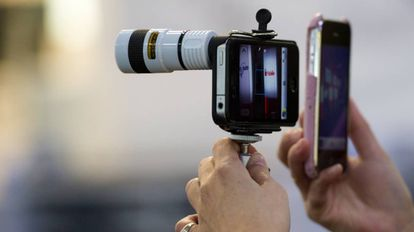 Una mujer usa un móvil con un teleobjetivo adaptado.