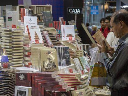 Un hombre ojea un libro en la FIL de Guadalajara.