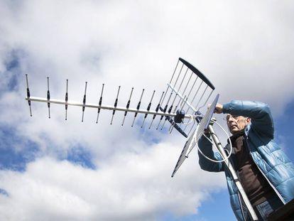 Un antenista cambia una antena antigua y resintoniza una nueva con amplificador de señal en una casa.