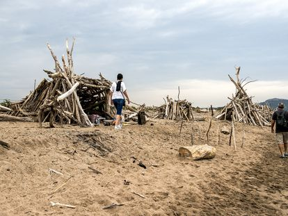 Una pareja de turistas pasea por las cabanas hechas con troncos en la Playa de la Gola del Ter de Torroella de Montgri