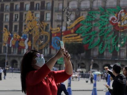 Una mujer toma una fotografía con su teléfono celular frente a la Catedral Metropolitana en el Zócalo de la Ciudad de México.