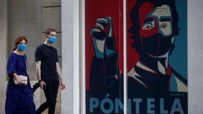 Dos personas pasean por delante de un graffiti con la imagen del director del centro de Coordinación de Alertas y Emergencias Sanitarias, Fernando Simón, en la puerta de un comercio de Barcelona