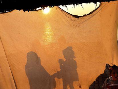 Una mujer da de comer a su hija en una tienda en Gaza, este domingo.