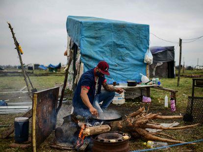 Un hombre cocina en un terreno ocupado por personas sin hogar en las afueras de Buenos Aires, Argentina, el 28 de agosto de 2020.