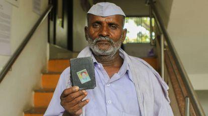 Raju Aage, de 55 años, enseña la fotografía de su hijo asesinado.