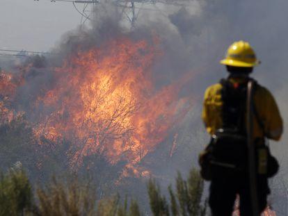 Un bombero monitorea las llamas en Santa Clarita, California, este lunes.