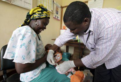 Iren Salama sostiene a su bebé Pendo mientras recibe una inyección como parte de un ensayo de vacuna contra la malaria en una clínica en la ciudad costera de Kilifi en Kenia, el 23 de noviembre de 2010.