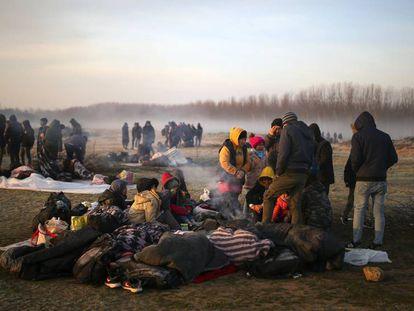 Unos migrantes se agolpan en la orilla del río Evros, este domingo cerca de Pazarkule (Turquía). En vídeo, un grupo de ciudadanos de Lesbos trata de impedir el desembarco de refugiados sirios.