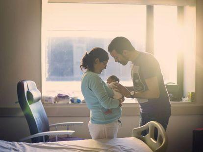 Dos padres miran a su recién nacido.