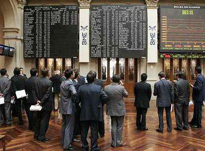 Un grupo de corredores de la Bolsa de Madrid observa la cotización de los valores del Ibex 35.