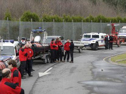Agentes de la Ertzaintza esperan junto a sus vehículos.