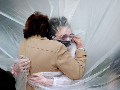 Una mujer abraza a su abuela a través de un paño de plástico colgado en un tendedero casero en Nueva York, el 24 de mayo de 2020.