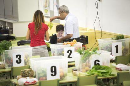 Un grupo de consumidores reparte los alimentos en las cestas durante el turno semanal de una cooperativa.