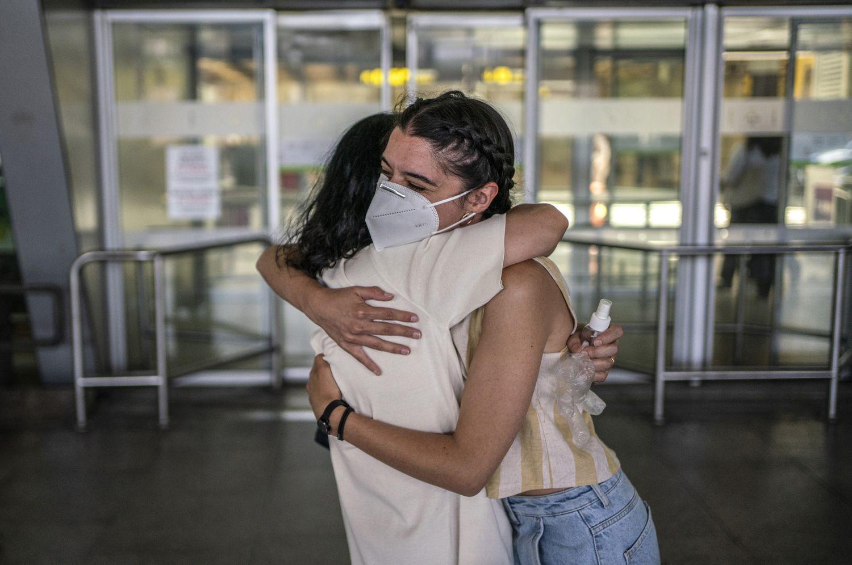 Una familia se abraza tras terminar el estado de alarma, en el aeropuerto de Barajas.