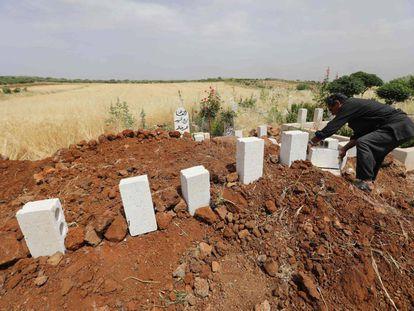 Un sirio coloca ladrillos sobre las tumbas de cinco civiles muertos en bombardeos sobre el poblado de Kafr Aweid, en la provincia de Idlib.