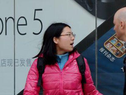 Una pareja camina por delante de una tienda de Apple en Pekín (China)