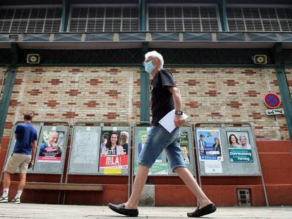 Un hombre camina en San Juan de Luz delante de carteles de las elecciones regionales francesas.