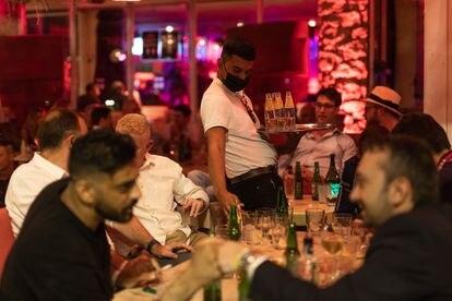Un camarero sirve a clientes de una discoteca del paseo marítimo de Barcelona, el 23 de septiembre.
