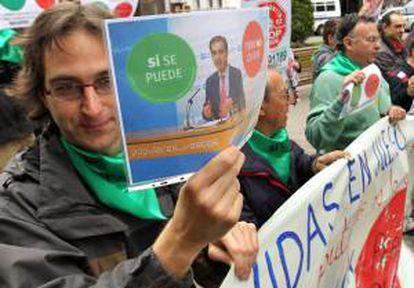 Integrantes de la Plataforma de Afectados por la Hipoteca de Bizkaia (PAH), muestran pancartas durante el escrache en Bilbao, cerca del domicilio del diputado del Partido Popular Leopoldo Barreda. EFE/Archivo