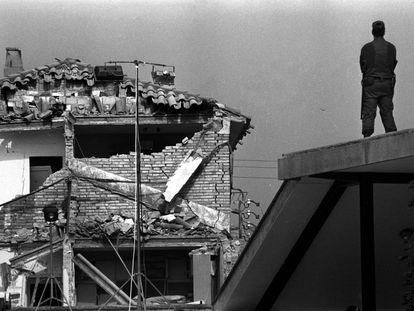 Un guardia civil, subido en el tejado de una casa, frente a las ruinas de la Casa Cuartel de Vic (Barcelona), después del atentado de ETA en mayo de 1991.