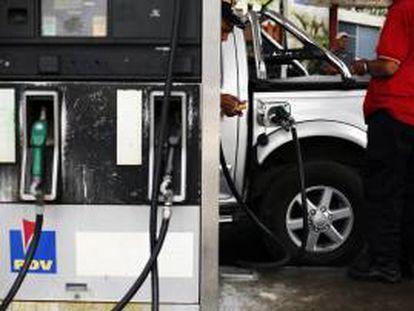 Un par de hombres trabajan en una estación de servicio de gasolina. EFE/Archivo