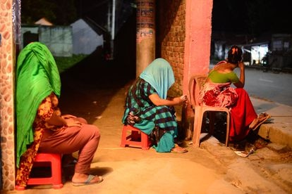 Tres trabajadoras sexuales esperan clientes junto al burdel de Kandapara.