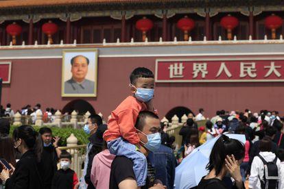 Un hombre y un niño con mascarillas visitan la entrada a la Ciudad Prohibida, en Pekín.