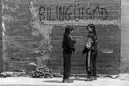Dos adolescentes conversan junto a una de las pintadas a favor del bilingüismo que aparecieron  en Barcelona en 1997.
