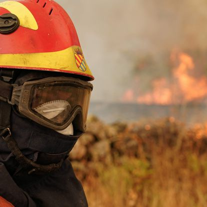 A firefighter operates at the site of a wildfire in Navalmoral de la Sierra near Avila, central Spain, on August 16, 2021. - A thousand people were evacuated and more than 5,000 hectares burned from 11am, with flames spreading up over a 40-kilometer perimeter. Spain saw its highest temperature on record on Saturday as a heatwave on the Iberian peninsula drove the mercury to 47.4 degrees Celsius (117.3 Fahrenheit), according to provisional data from the state meteorological agency. (Photo by CESAR MANSO / AFP)