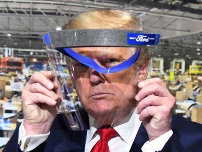 El presidente Trump se cubre con un escudo facial en una fábrica de Michigan, este jueves.
