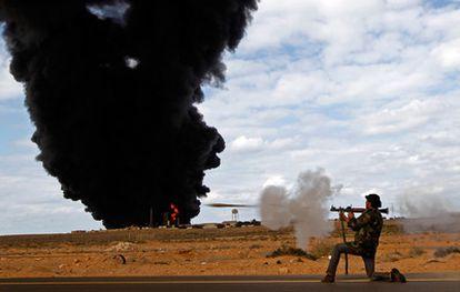 Un rebelde dispara una granada propulsada cerca de una terminal de gas, durante los combates entre Ras Lanuf y Bin Jiwad contra las fuerzas leales a Gadafi.