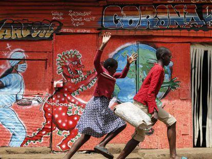 Dos niños corren por una calle frente a un mural informativo que advierte del peligro de la covid-19, en el barrio marginal de Kibera (Kenia).