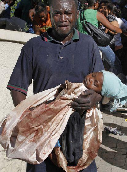 Un hombre herido, con el cadáver de su hija en brazos en Puerto Príncipe.