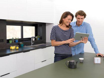 Una pareja utiliza el termostato inteligente Netatmo con una tableta de Apple.
