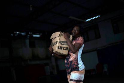 Una mujer carga una caja de alimentos de donación en una favela de Río de Janeiro, este martes.