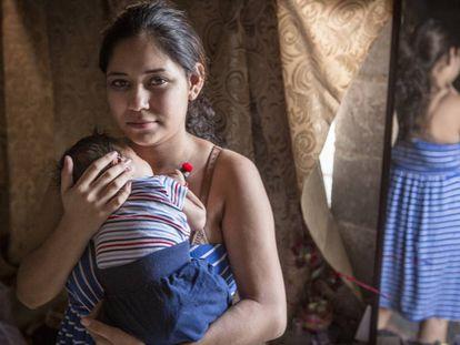 Brissa, de 15 años, sostiene en brazo a su hijo de tres semanas de edad en la casa de su madre en Sinaloa, México.
