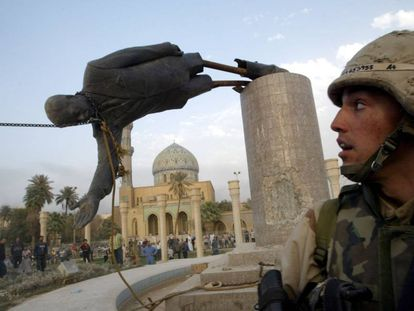 Un soldado estadounidense observa cómo derriban la estatua del presidente iraquí Sadam Husein, en abril de 2003.