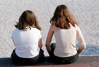 Dos chicas, sentadas en un paseo marítimo.